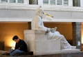 """A student sits next to a statue at Ludwig Maximilian University of Munich. The sign affixed to the statue's nose roughly translates as """"Education lies."""""""